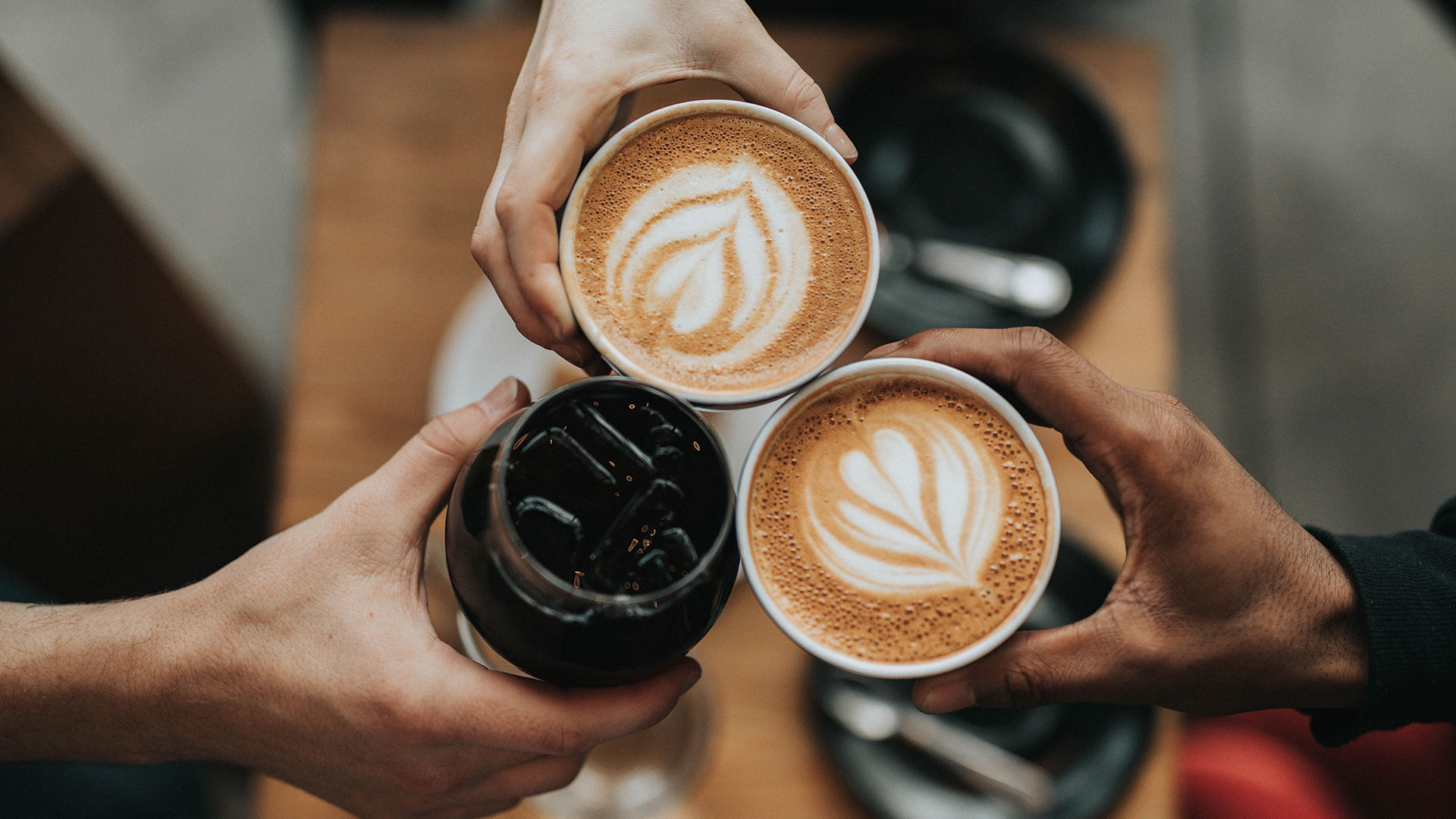 Young people's hands holding coffee cups
